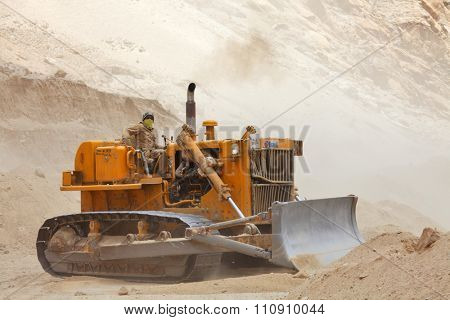 SRINAGAR â?? LEH ROAD, JAMMU & KASHMIR, INDIA - JUNE 09, 2015:  Bulldozer doing mountain road repair and construction works after landslide  in Himalayas