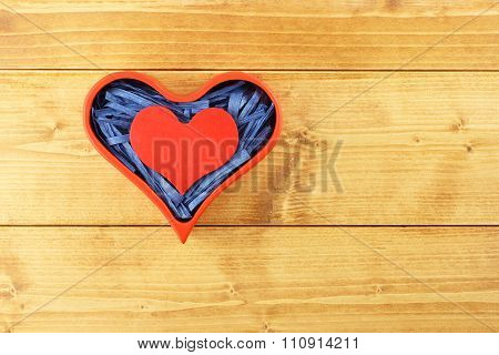 Red painted wooden heart enclosed with blue paper raffia strips in red box on wooden background