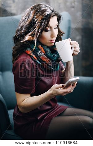 Beautiful girl with beautiful makeup drinking tea or coffee in cafe and looking at the phone.