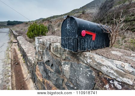 Black Mailbox With Red Flag On Stone Wall