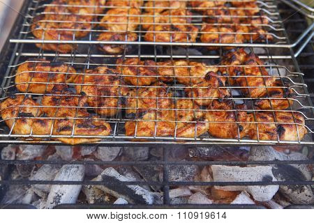 fresh raw chick in meat holder on grid grill over burned charcoal spiced with salt pepper paprika ready to serv party