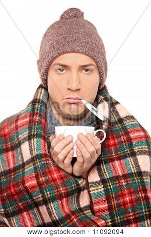 Ill Man Covered With Blanket Holding A Tea Cup