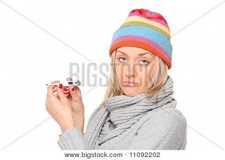 Mulher doente com termômetro em suas mãos