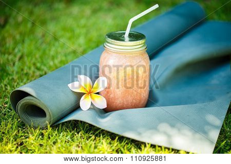 Smoothies And Yoga Mat On The Grass