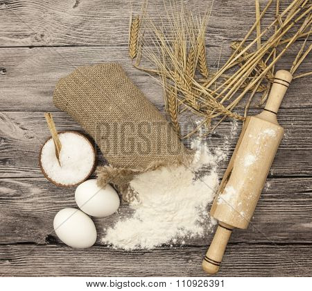Wheat flour in a canvas bag, with spikelets of rye, a large salt shaker wood, raw eggs, a wooden rolling pin: set for making homemade bread dough on a beautiful dark wooden background.