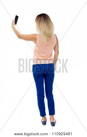 back view of standing young beautiful  woman  and using a mobile phone. girl  watching.   Isolated over white background. Blonde in blue pants makes self holding the phone in your left hand.