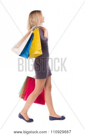back view of going  woman  with shopping bags . beautiful girl in motion.  backside view of person.  Isolated over white background. Girl in a short dress is right throwing shoulder paper bags.