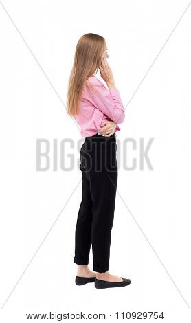 back view of standing young beautiful  woman.  girl  watching. Rear view people collection.  backside view of person.  girl office worker in black trousers stands sideways and looks thoughtfully left