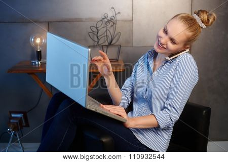 Busy young woman talking on mobilephone while using laptop computer.