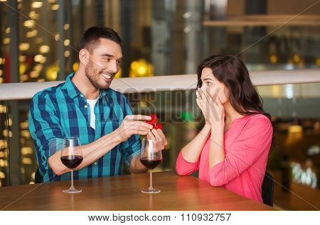 people, proposal, love, couple and holidays concept - smiling man giving diamond engagement ring to his happy girlfriend at restaurant