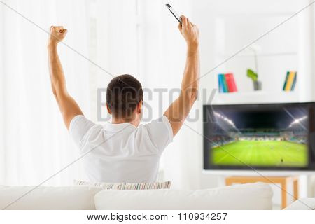 leisure, technology, media, sport and people concept - man watching football game on tv and supporting team at home from back