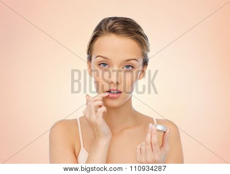 beauty, people and lip care concept - young woman applying lip balm to her lips over beige background