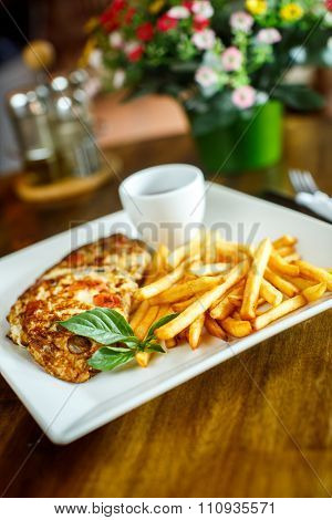 Scrambled Eggs And French Fries On A Wooden Table
