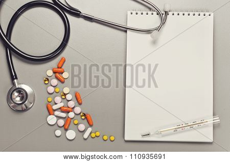 Open Notebook With Blank Pages, Pills, Capsules, Thermometer And Stethoscope