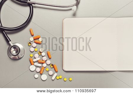 Open Notebook With Blank Pages, Pills, Capsules And Stethoscope