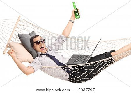 Young overjoyed businessman lying in a hammock with a beer in his hand and working on a laptop isolated on white background