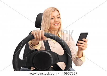 Studio shot of an irresponsible blond woman texting and driving isolated on white background