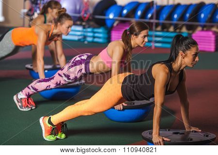 Women balancing on bosu ball