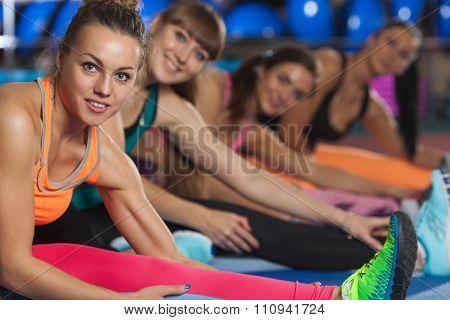 Women stretching legs in sports club