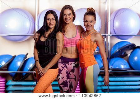 women in gym are posing and smiling to the camera.