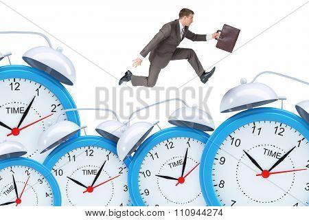 Businessman running with set of alarm clocks