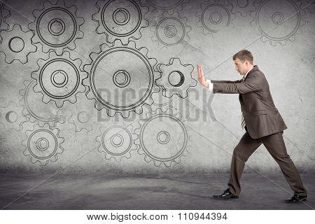 Businessman pushing cog wheel