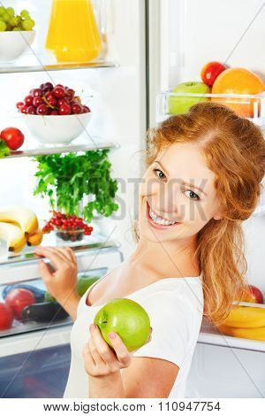 Happy Woman With Apple And Open Refrigerator With Fruits, Vegetables And Healthy Food