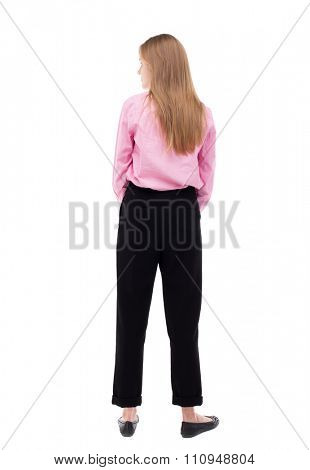 back view of standing young beautiful  woman.  girl  watching. Rear view people collection.  backside view of person.  The girl office worker in black trousers looks to the left.