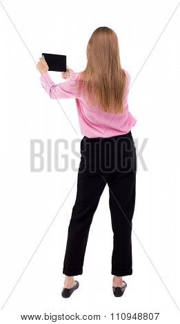 back view of standing young beautiful girl with tablet computer in hands of. girl  watching. Isolated over white. girl office worker in black trousers turning left takes something on smartphone
