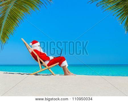 Christmas Santa Claus At Palm Beach Deckchair Working At Computer