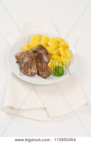 plate of pan fried potatoes and chicken liver on white place mat