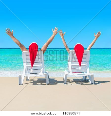 Couple In Santa Hats Relaxing At Tropical Beach On Deckchairs