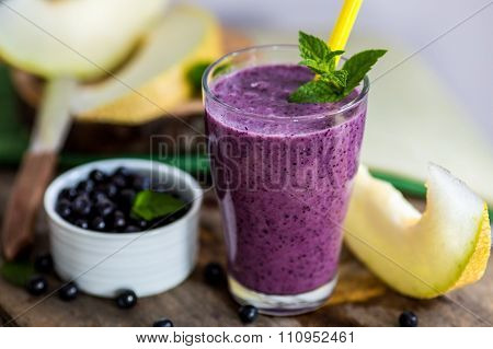 Blueberry Smoothie In A Glass With A Straw And Sprig Of Mint, Over Vintage Wood Table With Fresh Ber