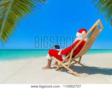 Christmas Santa Claus At Beach In Deckchair Work Using Laptop