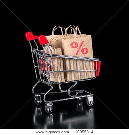 Concept Of Shopping Trolley With Paper Bags Is Isolated On Black Background