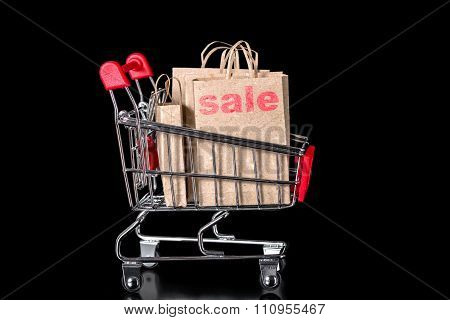 Closeup Shopping Cart With Sale Paper Bags Is Isolated On Black Background