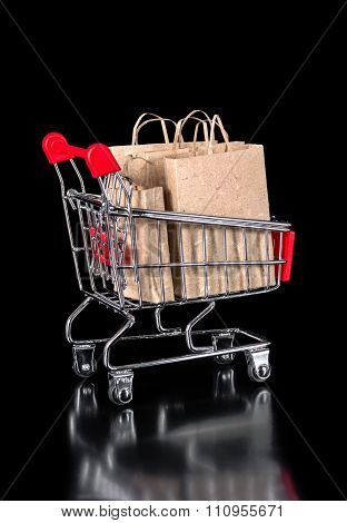 Shopping Trolley With Eco Paper Bags Is Isolated On Black Background