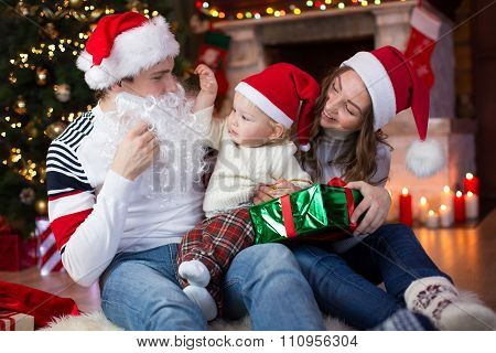 Surprised child looks at dad weared Santa Claus with fake beard sitting opposite Christmas tree