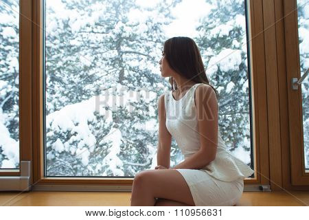 elegant young woman in white short dress sit at home by the window looking snow fall through the glass