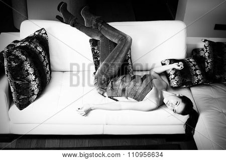 young attractive woman in tight jeans and top, lie on leather sofa, full body shot, black and white photo