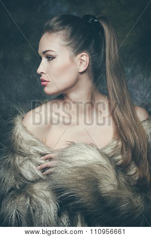 winter is coming, beautiful young woman with artificial fur  portrait, studio shot, profile