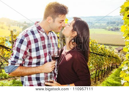 Couple Drinking And Kissing In A Vineyard