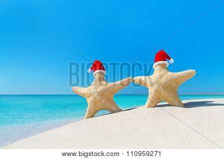 Couple Of Sea-stars  In Red Santa Hats Walking At Tropical Beach