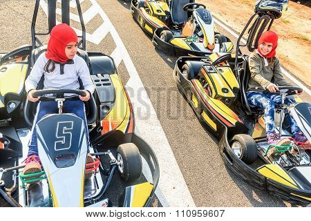 Little Girls Preparing To Drive  Go- Kart Car In A Playground Racing Track