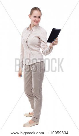 front view of standing young beautiful  girl with tablet computer in the hands of. girl  watching.  Isolated over white background. A girl in a white jacket smiling read e-books.