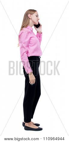 side view of a woman walking with a mobile phone. back view ofgirl in motion.   Isolated over white background. Woman office worker in a pink shirt standing right side talking on phone.