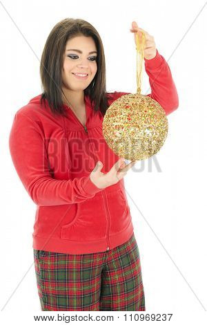 A beautiful teen girl in her pajamas admiring a giant, golden Christmas bulb.  On a white background.