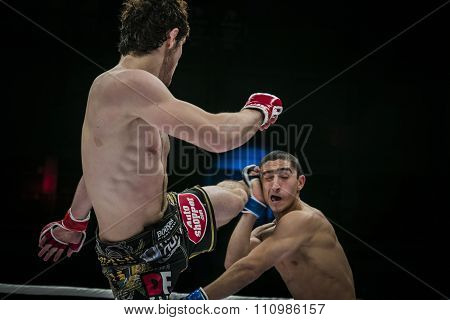 athlete mixed martial arts fighter strikes his foot on head of his opponent