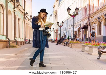 Smiling girl in retro outfit holding city map