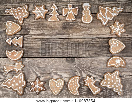 Christmas framework arranged from seasonal shape gingerbread cookies with white icing placed on wooden rustic boards